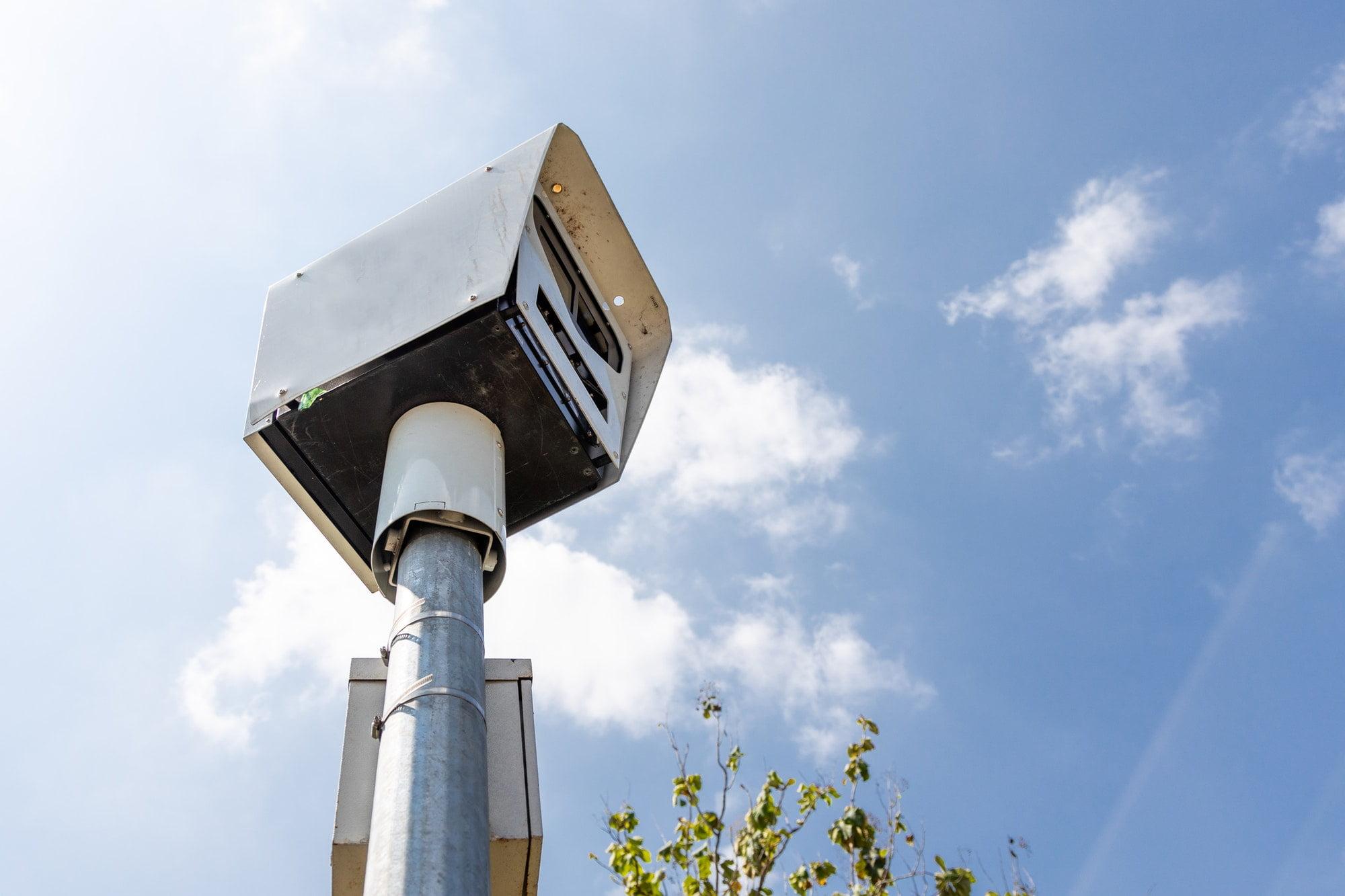 Close-up on speed trap surveillance camera along highway.